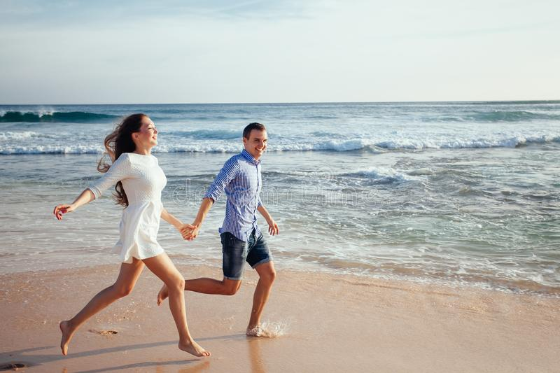 Happy cheerful couple having fun running to the ocean together and doing splashes of water on a tropical beach at sunset royalty free stock photography