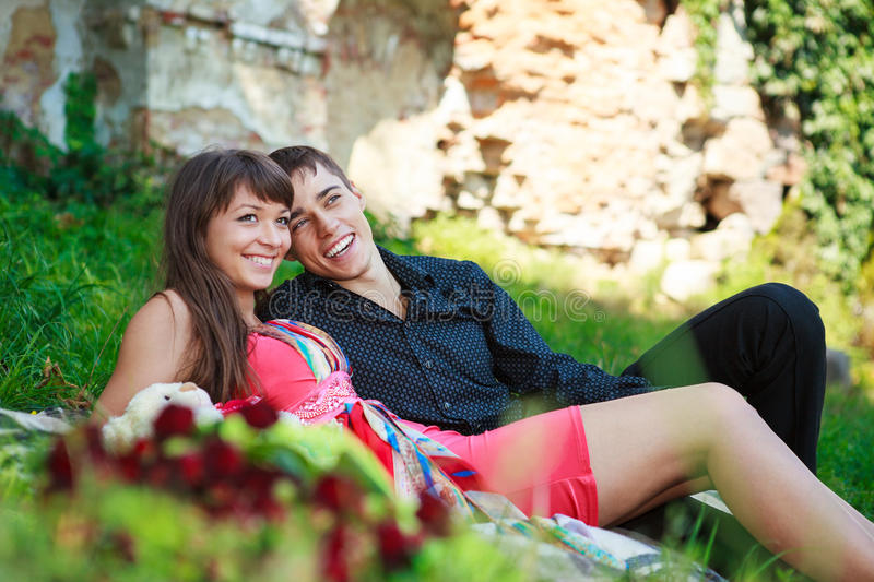 Happy Cheerful Couple Lying On Green Grass And Laughs Royalty Free Stock Photography