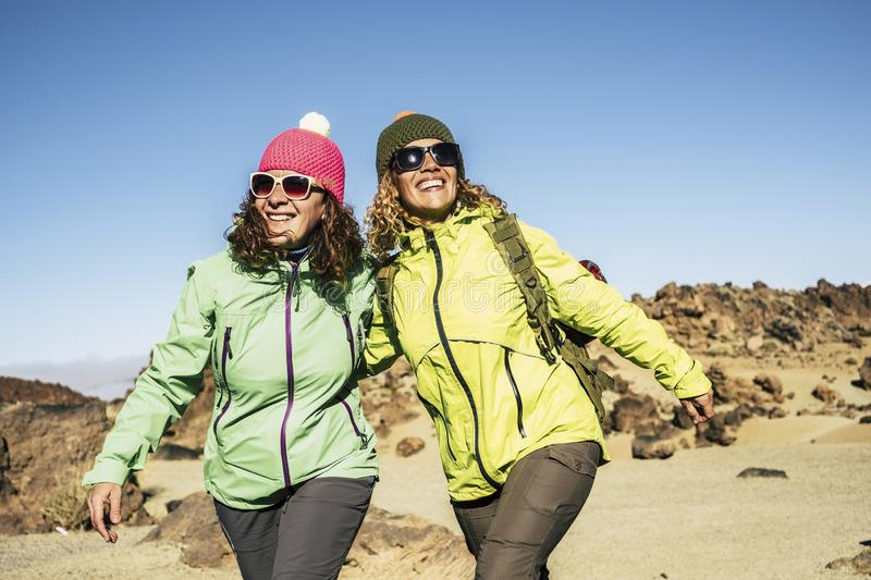 Happy cheerful couple of middle age women friends walking together at the mountain for alternative vacation - sunny day in outdoor. Leisure activity in the royalty free stock image