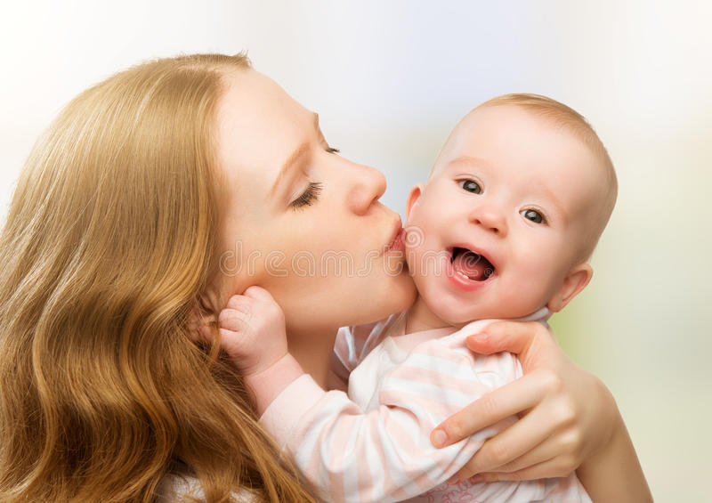 Happy cheerful family. Mother and baby kissing stock images