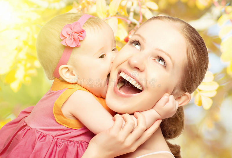 Happy cheerful family. Mother and baby kissing in nature outdoor royalty free stock photography