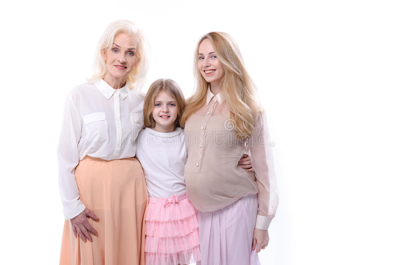 Happy cheerful family standing together. Connection between generations. Female persons of different ages are hugging and looking at camera with bright smiles royalty free stock photos