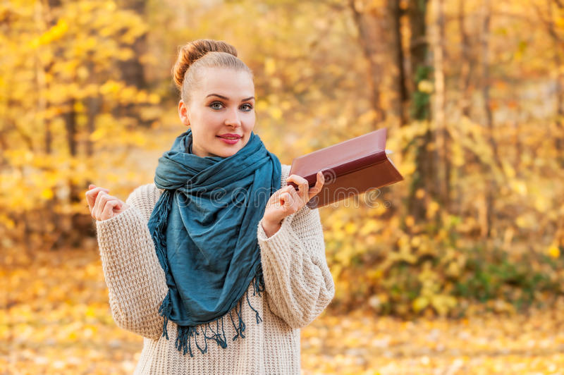 Happy cheerful female just finished reading. A book outside in the forest royalty free stock photo