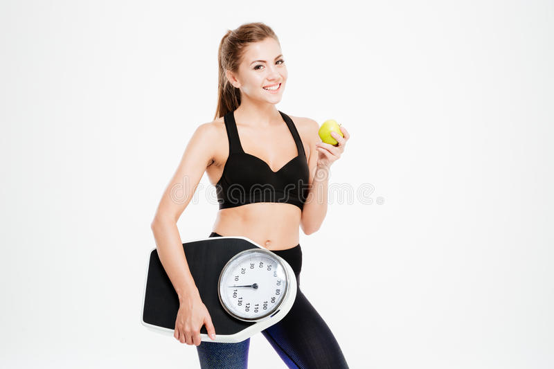 Happy cheerful fitness woman holding weight scales and green apple stock photography