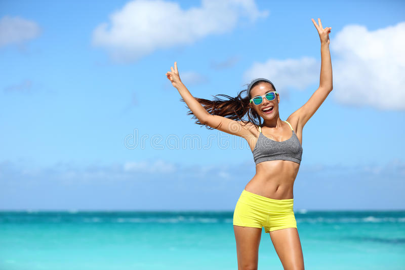 Happy cheerful fitness woman in sunglasses winning arms up doing v hand signs royalty free stock photo