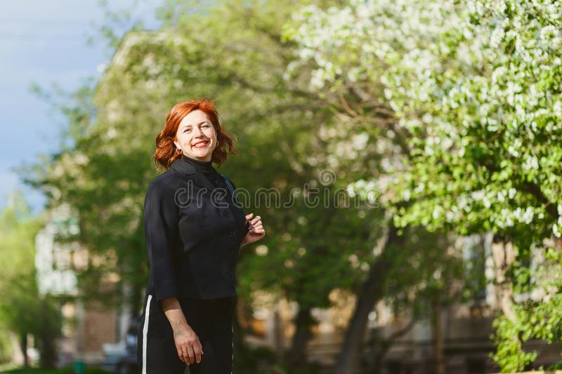 Happy cheerful forty-year-old woman in a black suit outdoor royalty free stock photo