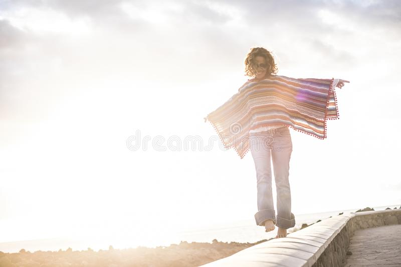 Happy cheerful free people enjoy the outdoor -woman walking in balance smiling with coloured hippy trendy style mexicn poncho -. Concept of leisure activity and royalty free stock images