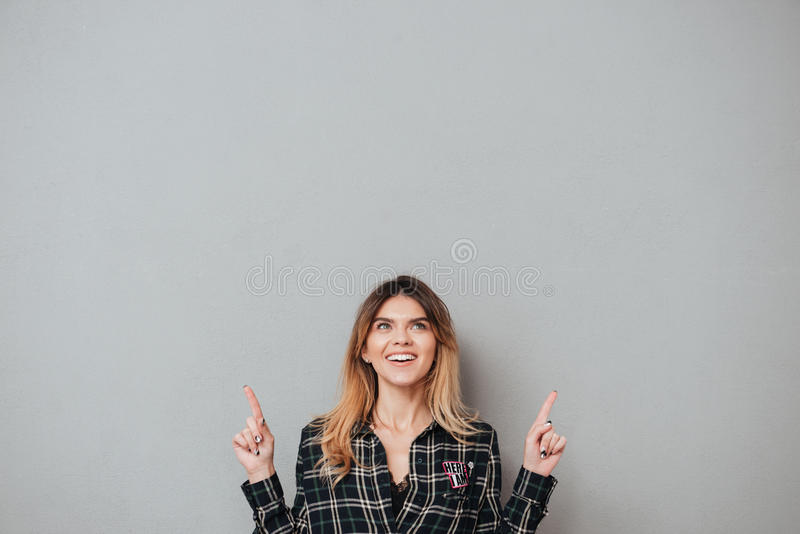 Happy cheerful girl pointing two fingers up at copy space stock images