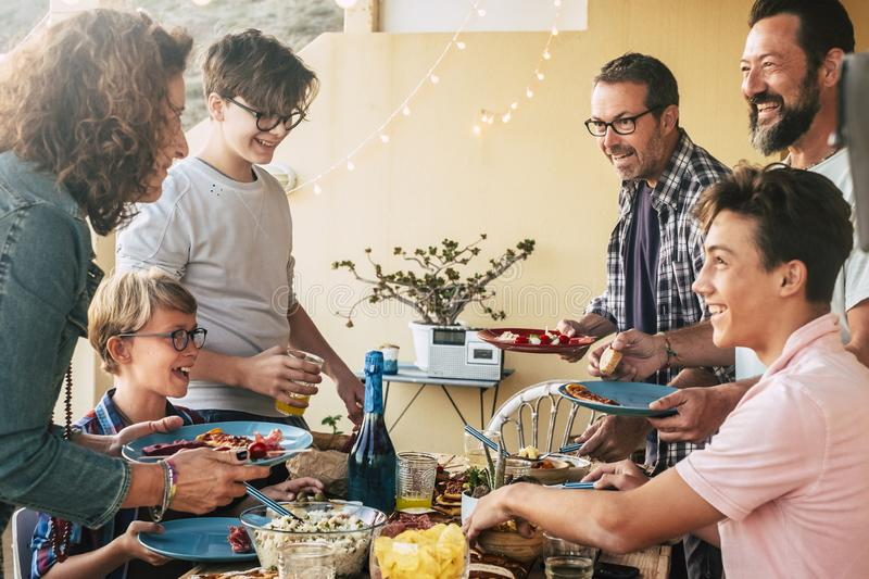 Happy cheerful group of caucasian people mixed generation and ages have fun together having dinner or lunch together - concept of. Party and friendship for stock image