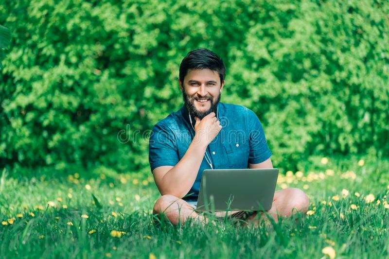 Happy cheerful hipster man with a laptop sitting outdoors on green grass stock image
