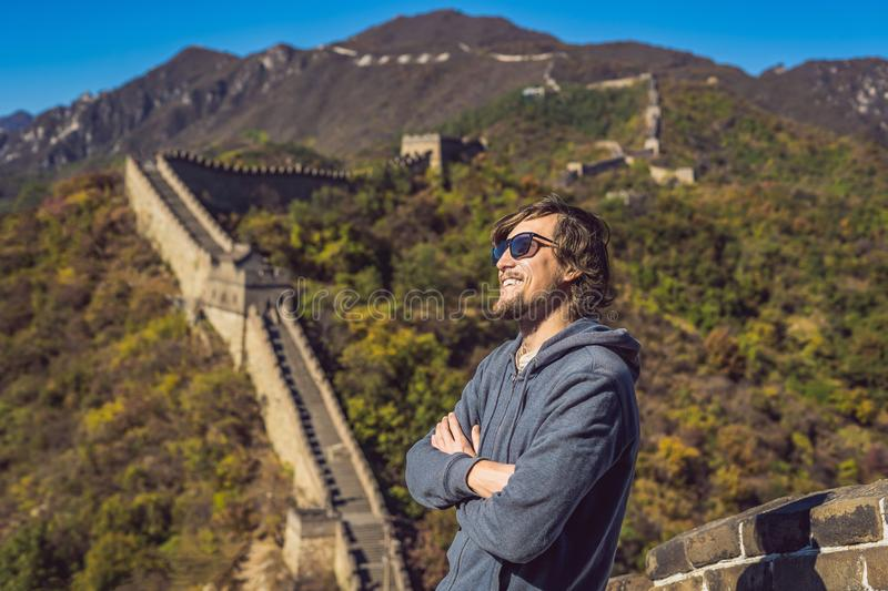 Happy cheerful joyful tourist man at Great Wall of China having fun on travel smiling laughing and dancing during royalty free stock photos