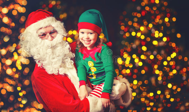 Happy cheerful laughing child elf helper and Santa Claus at Christmas. Happy cheerful laughing child elf helper in the hands of Santa Claus at Christmas stock photo