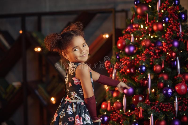 Preschool cheerful little happy girl have a good time at home near bright christmas tree with lights royalty free stock image