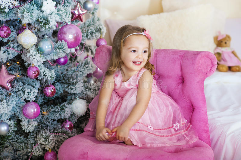 Happy cheerful little girl excited at Christmas Eve, sitting under decorated illuminated Tree. Greeting card or cover royalty free stock image