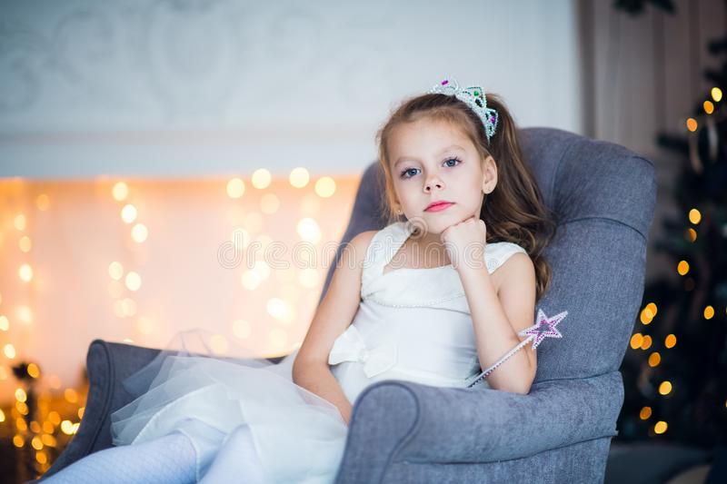 Happy cheerful little girl wearing crown excited at Christmas Eve, sitting under decorated illuminated Tree. Greeting stock photos