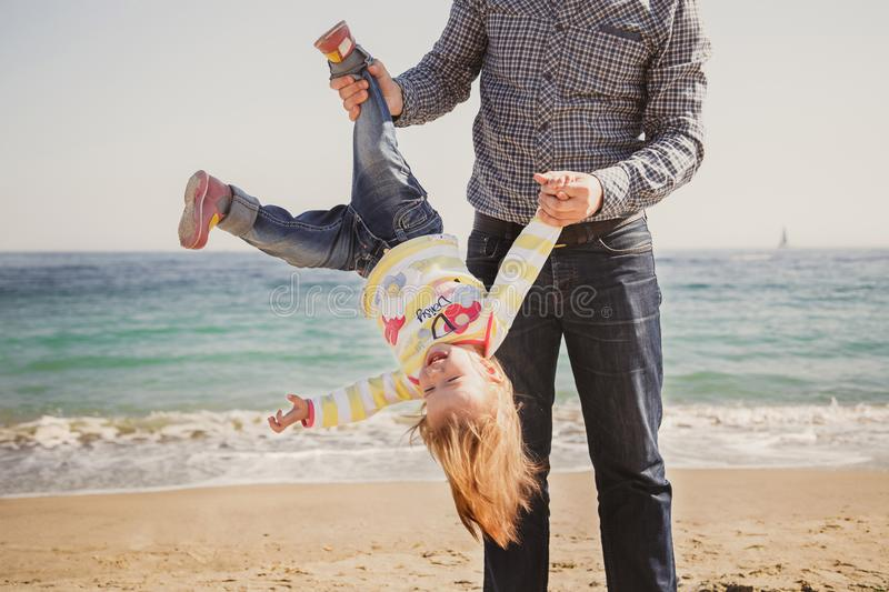 Happy cheerful loving family, father and little daughter playing on beach, young father is holding his kid upside down stock photography