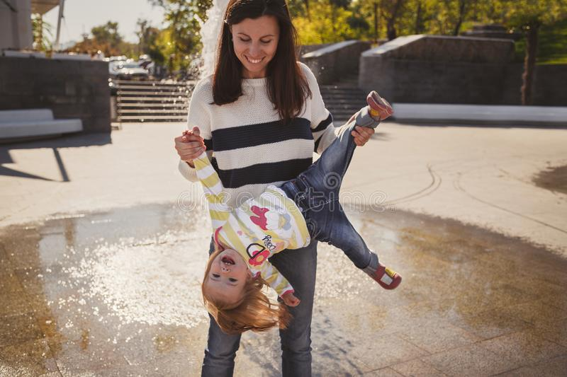 Happy cheerful loving family, mother and little daughter playing in park next to fountain, young mother is holding small girl royalty free stock photo