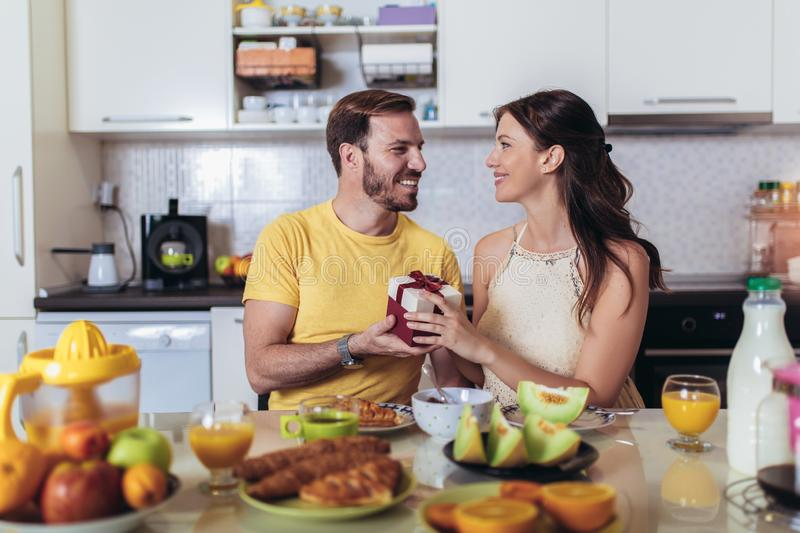 Cheerful man surprising his girlfriend with a gift at home in the kitchen while breakfast. Happy cheerful men surprising his girlfriend with a gift at home in stock images