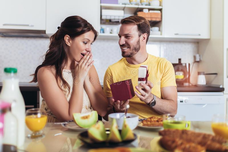 Cheerful man surprising his girlfriend with a gift at home in the kitchen while breakfast. Happy cheerful men surprising his girlfriend with a gift at home in royalty free stock images