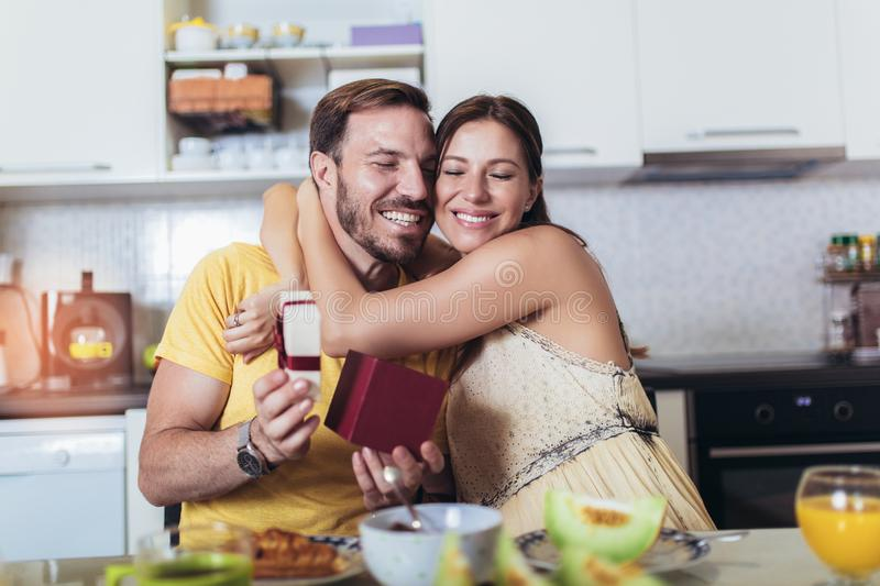 Cheerful man surprising his girlfriend with a gift at home in the kitchen while breakfast. Happy cheerful men surprising his girlfriend with a gift at home in stock photos