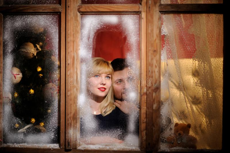 happy cheerful man and woman looking through the frozen window stock photo