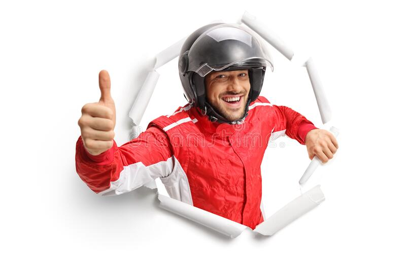Happy cheerful racer with a helmet peeking through a torn paper hole and showing a thumb up royalty free stock photography