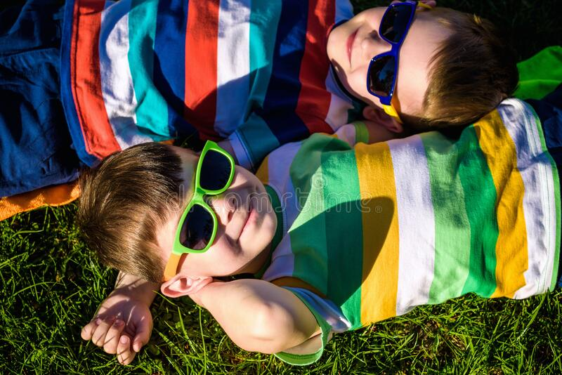Happy cheerful smiling children, laying on a grass, wearing sunglasses, smiling at the camera, shot from above royalty free stock image
