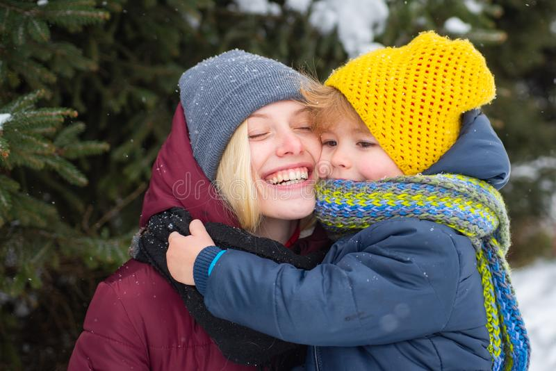 Happy cheerful smiling mother with her cute kid at snowy background. Snow-covered forest path. Winter holidays. Amazing stock photography