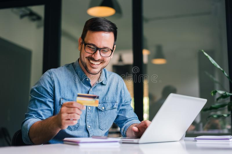 Happy cheerful smiling young adult man doing online shopping or e-shopping satisfied entrepreneur making online payment paying for royalty free stock image