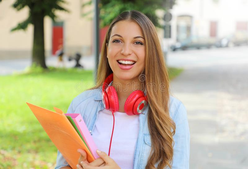 Happy cheerful student girl holding folders outdoors looking at camera.  royalty free stock photos