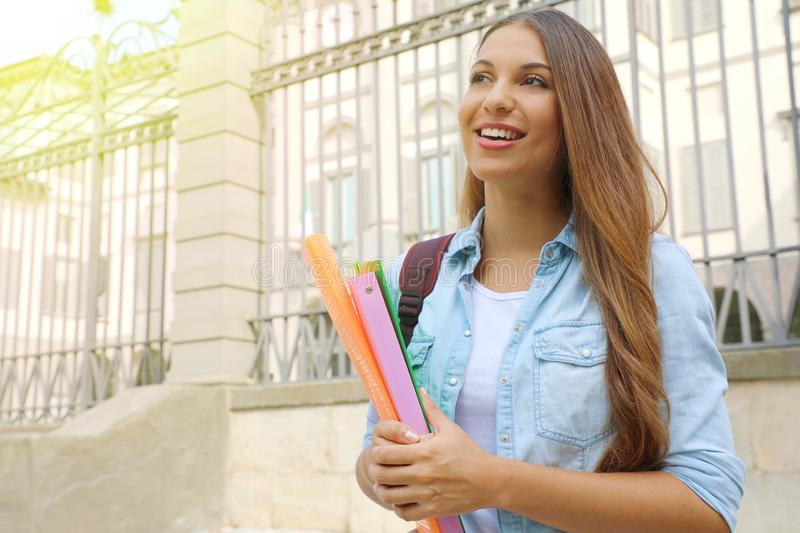 Happy cheerful student girl holding folders outdoors looking to the side the copy space.  stock images