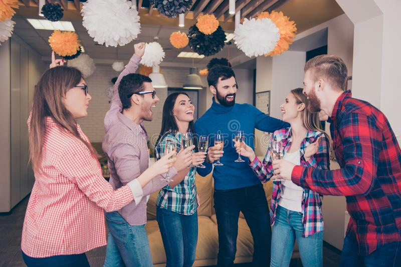 Happy cheerful student`s team having party with champagne. Handsome attractive cheerful glad nice pretty beautiful excited rejoic stock photo