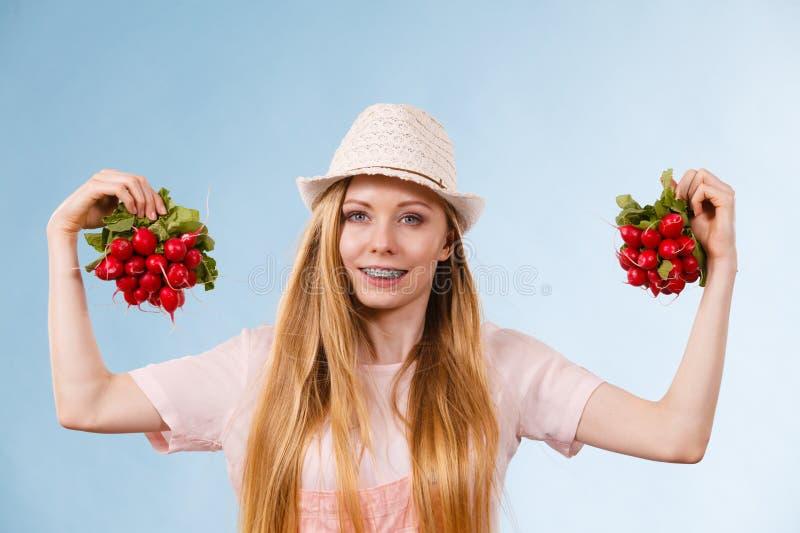 Happy woman holding radish royalty free stock images