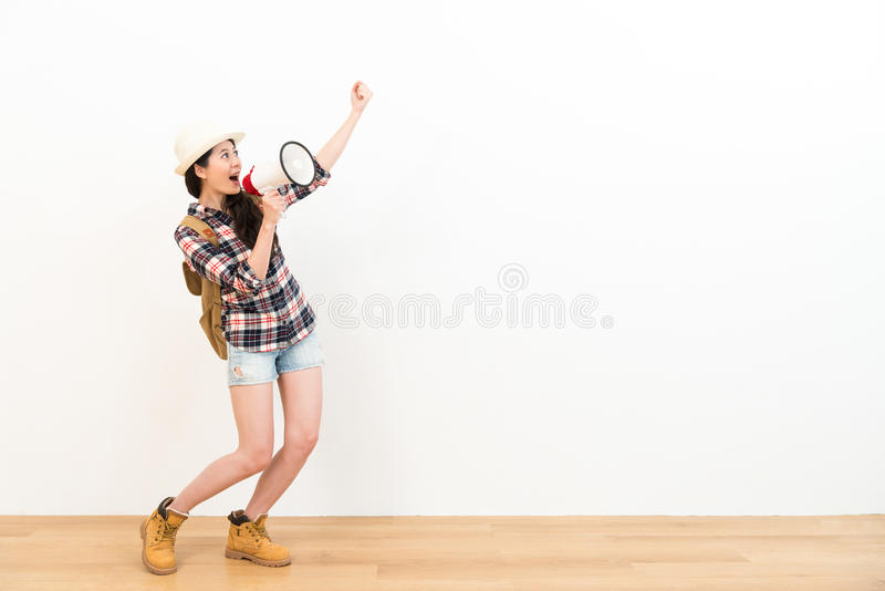 Happy cheerful woman looking at white background. Making victory winner celebrate gesture and using loudspeaker announced information on wooden floor royalty free stock photo