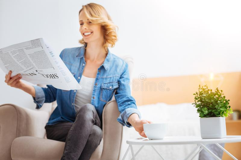 Happy cheerful woman reading her favorite newspaper and smiling stock photography