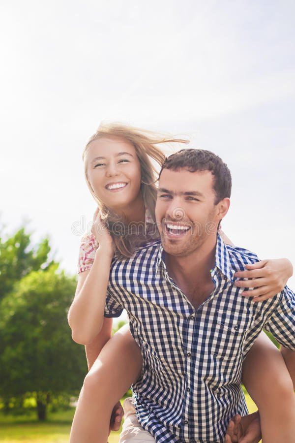 Happy and Cheerful Young Caucasian Couple Piggybacking Outdoors. royalty free stock photography
