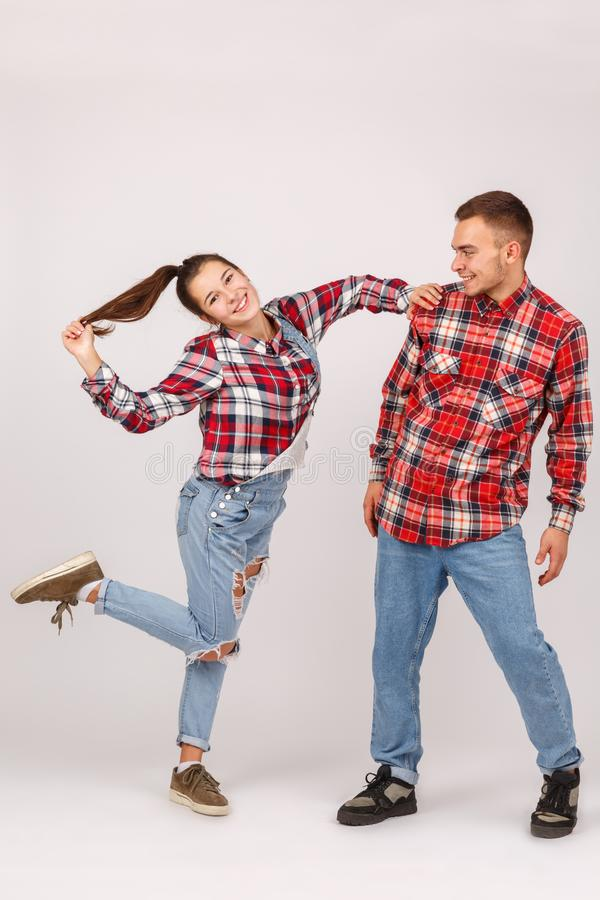 A cheerful young couple. The girl leans on the guy and holds her hair. Insulation. stock photo