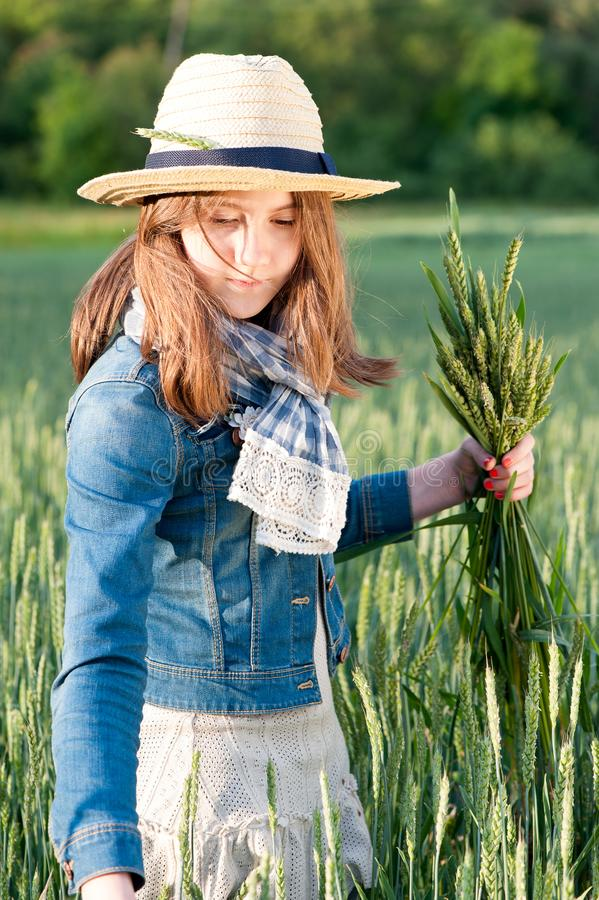 Happy young girl in summer hat picking stems on wheat field. Happy cheerful young girl in summer hat collecting stems in rays of sunlight on wheat field. Multi stock photo