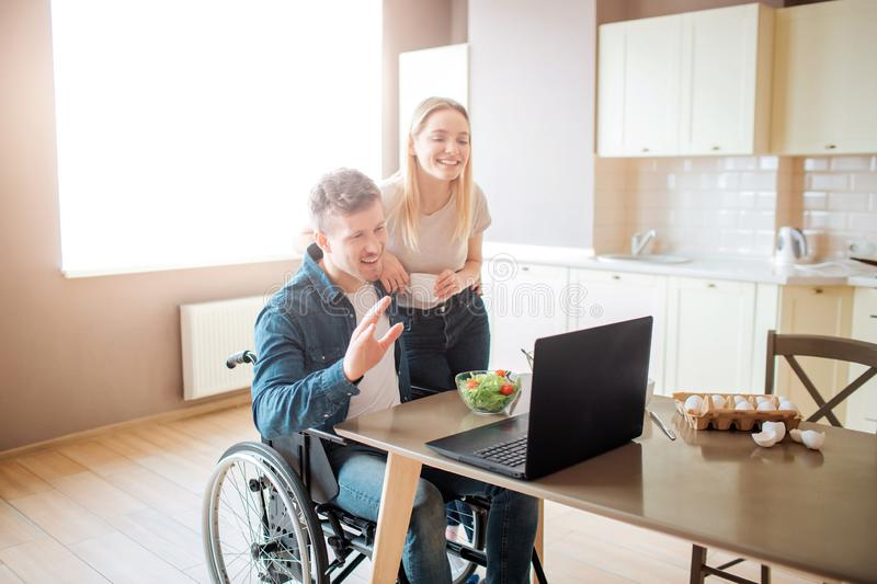 Happy cheerful young man sit at table and look on laptop. Guy with disability and inclusiveness. Young woman stand stock images