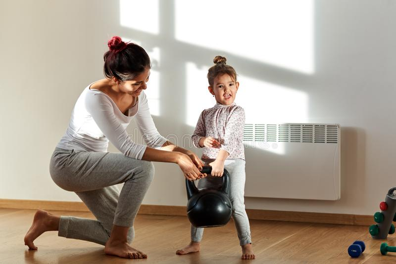 Happy and cheerful young teenage girl raises the child with his mother a heavy weight. Funny facial expression stock images