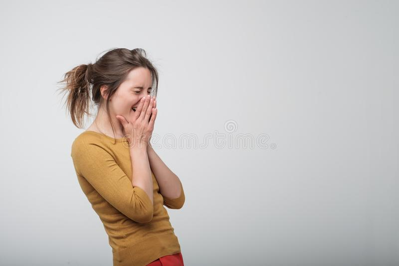 Happy cheerful young woman laughing and closing her hands. royalty free stock photos