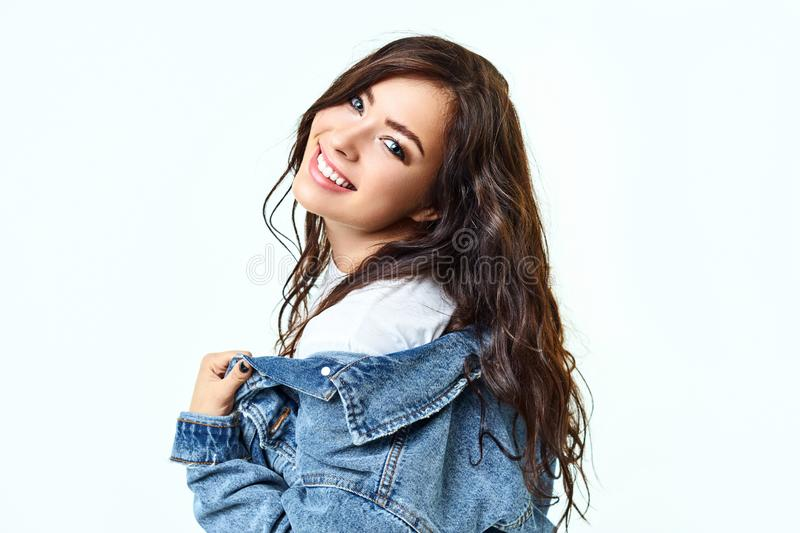 Happy cheerful young woman, looking at camera with joyful and charming smile. Brunette girl with a perfect white-toothed royalty free stock photo