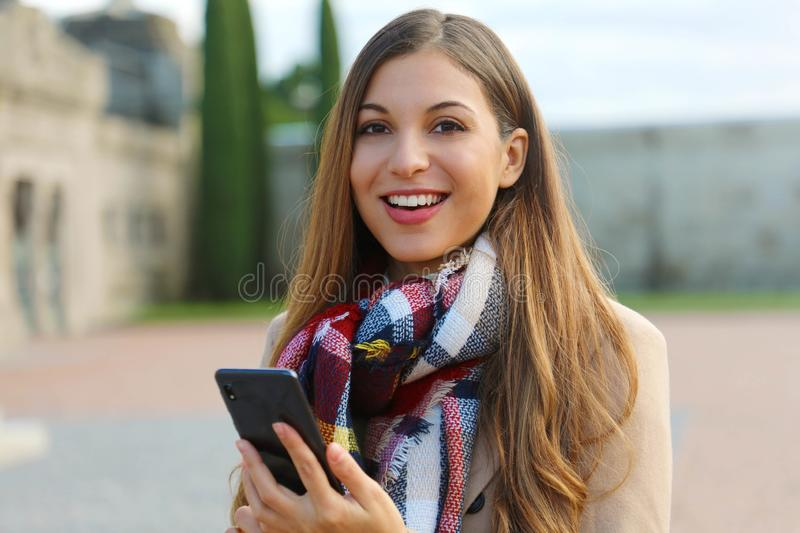 Happy cheerful young woman looks at you holding mobile phone on city square wearing coat and scarf in winter stock images