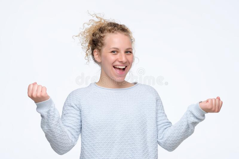 Happy cheering woman raises hands with excitement, screams yes, being lucky. People, success, achievement and joy concept. Happy cheering curly woman raises stock photos