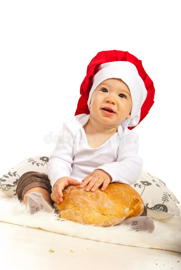 Happy chef baby with bread. Happy chef baby with round bread sitting down royalty free stock image