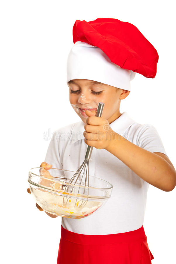Happy chef boy mixing dough royalty free stock image