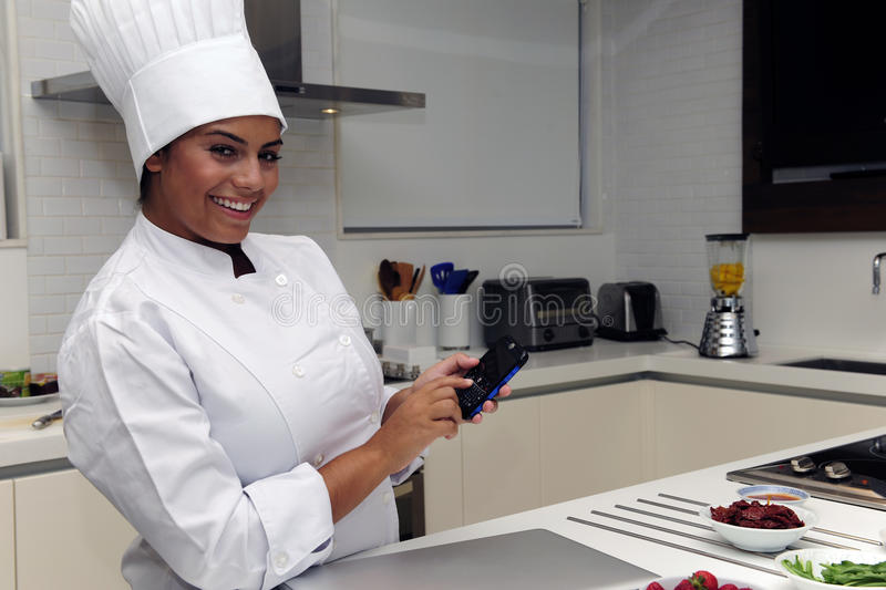 Happy chef with cellphone. Happy chef cooking in kitchen and typing sms on cellphone stock photos