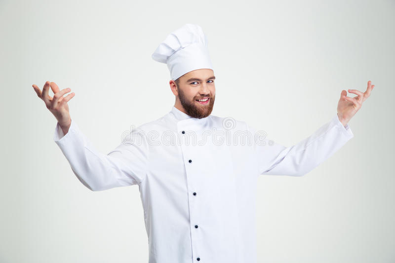 Happy chef cook showing welcome gesture. Portrait of a happy chef cook showing welcome gesture isolated on a white background royalty free stock photography