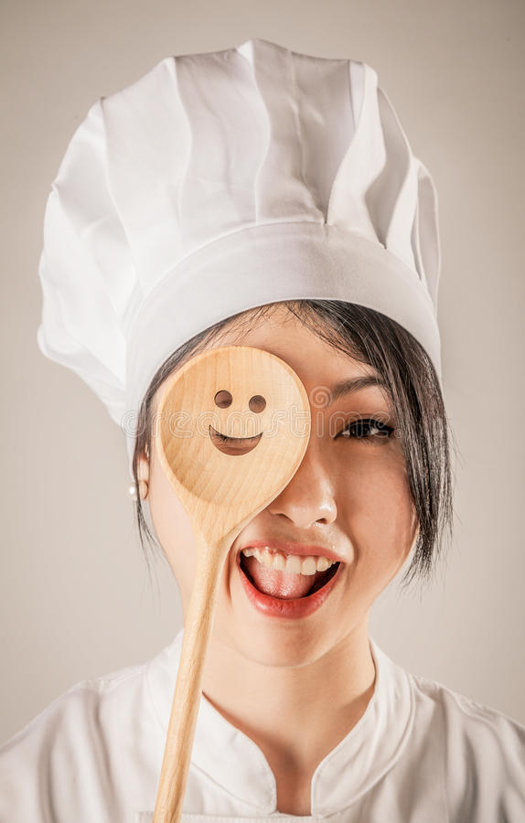 Happy Chef Covering One Eye with Wooden Ladle. Close up Happy Young Female Chef Covering One of her Eye a Wooden Ladle with Happy Face Design. Isolated on Brown stock photo