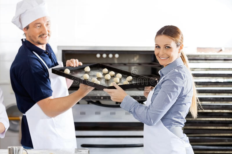 Happy Chef Giving Baking Sheet To Colleague In royalty free stock photography